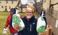 An ICA Food Shelf volunteer holds up two turkeys for Thanksgiving dinner.