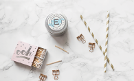 Matches, an Excelsior Candle Co. candle and two gold and white straws.