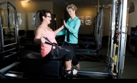 Shawn Marquis, right, assists Jennifer Barada on a Pilates machine.