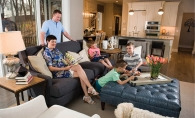 The Musgjerd family in their living room: Scott and Melissa with Lucas (in green), Daniel (in stripes), Jake (in coral) and Tilley the dog.