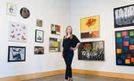 Anna Wander, member of the 2019 Senior Spotlight, stands in front of a wall of art.