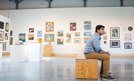 Jai Chadha, part of the 2019 Senior Spotlight, sits in front of a wall of art.