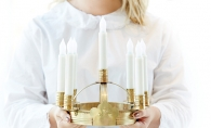 A performer in the American Swedish Institute's St. Lucia concert holds a candle crown