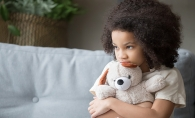 A stressed child holds a teddy bear.