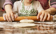 A grandmother helps her granddaughter roll some dough.