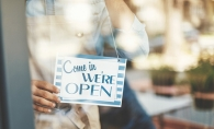 "A shop celebrating Small Business Saturday hangs a ""Come in we're open"" sign in the window."