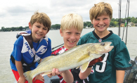Three boys hold a walleye they caught from Lake Minnetonka, thanks to the help of the Westonka Walleye Program.