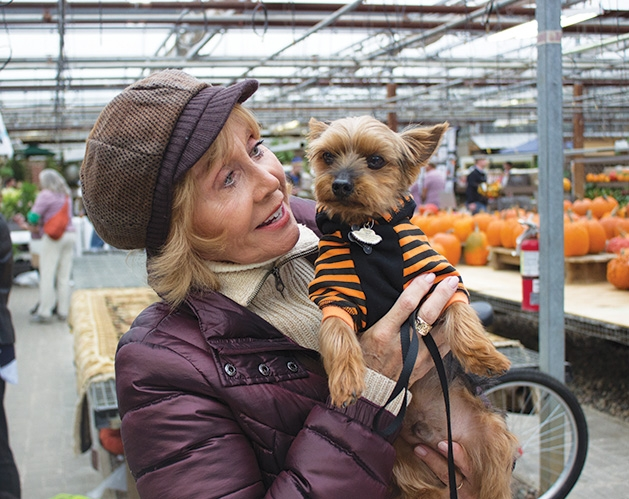 A woman holds a dog at Tonkadale Greenhouse's Biscuits & Blooms event.