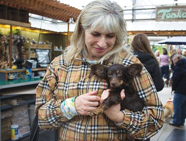 A woman holds her dog at Tonkadale Greenhouse's Biscuits & Blooms event.