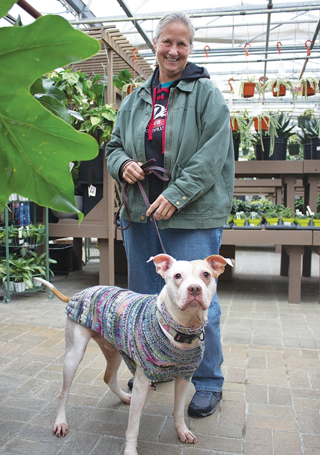 A woman holds her dog on a leash at Tonkadale Greenhouse's Biscuits & Blooms event.