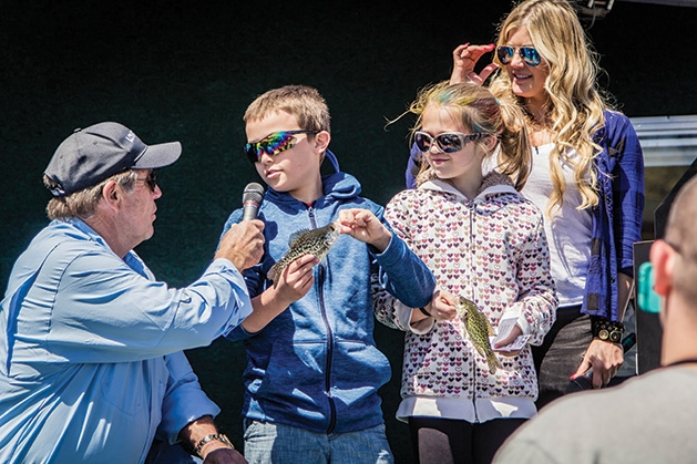 A boy and girl hold up their catches while being interviewed at the 51st Annual Minnesota Bound Crappie Contest