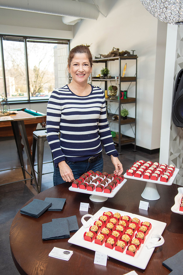 Regina Donnage, a member of the Twin Cities Wedding & Event Professionals, poses with some chocolate treats.