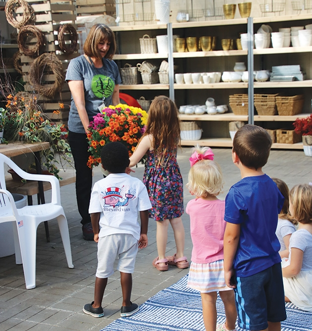 A woman hands out flowers to children at Tonkadale Greenhouse's Third Thursdays event.