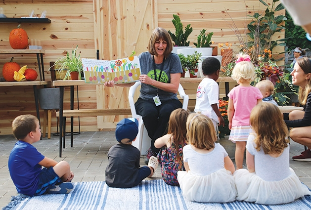 A woman reads to children at Tonkadale Greenhouse's Third Thursdays event.