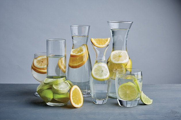 A collection of picthers containing fruit water.