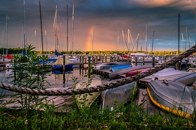 Rainbows paint the sky over boats on Lake Minnetonka.