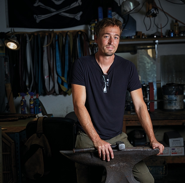 Jason Kraus, owner of Northstar Forge knife-making business, stands with his forging equipment