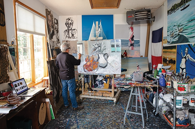 Local artist Richard Merchan paints in his studio in Greenwod