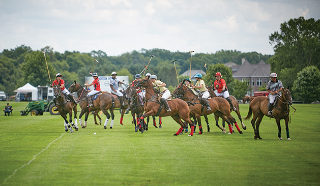 Riders on horses go for the ball during a Twin City Polo Club match.
