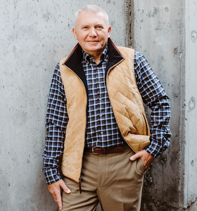 Judd Frost poses wearing a blue button-down, vest and khakis.