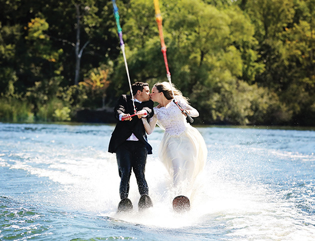 A Minnetonka couple water skis in their wedding attire for their unique save-the-date photo.