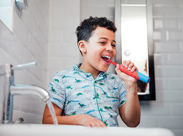 A boy brushes his teeth with an electric toothbrush.