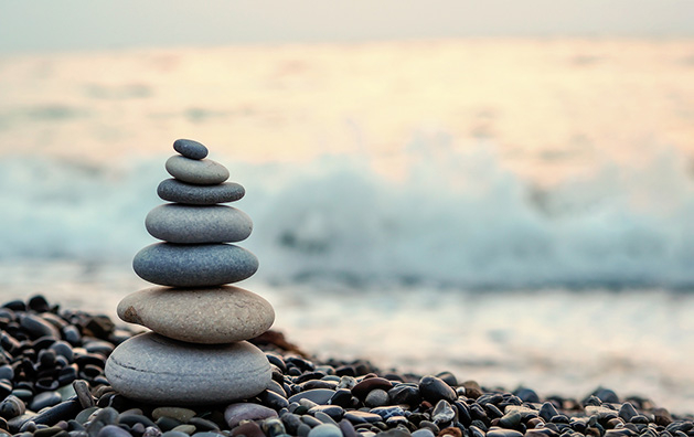 A stack of balanced rocks on a shoreline, a metaphor for achieving a balanced life.