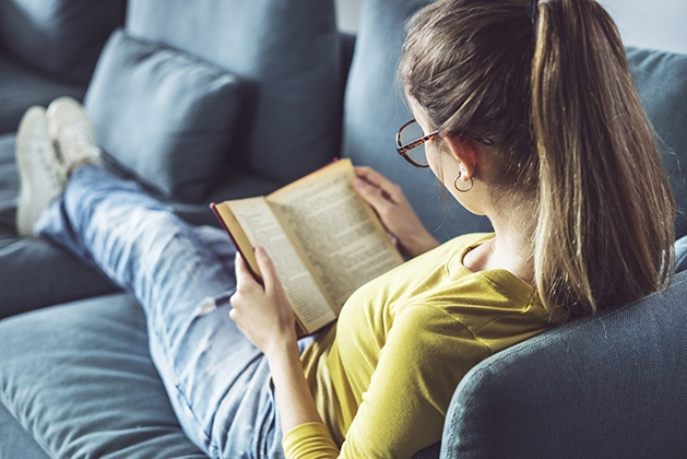 A teenage girl reads a YA novel on her couch.