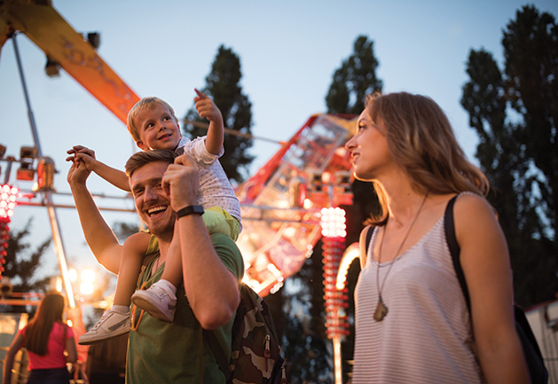 A man and woman with their son at a destination music festival.