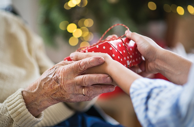Someone hands a senior a gift from the Be a Santa to a Senior program.