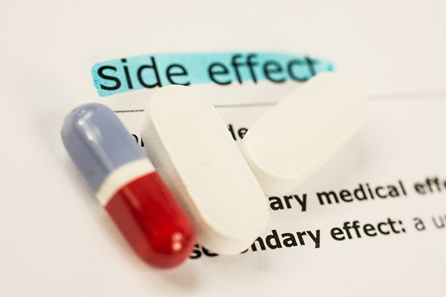 Three pills rest on a piece of paper listing side effects.
