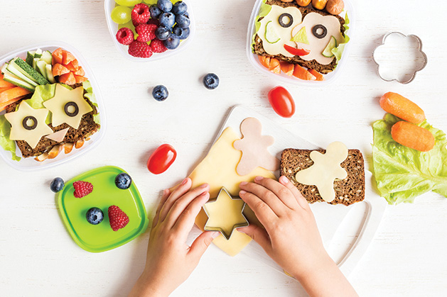 A child uses a cookie cutter to make fun sandwiches.