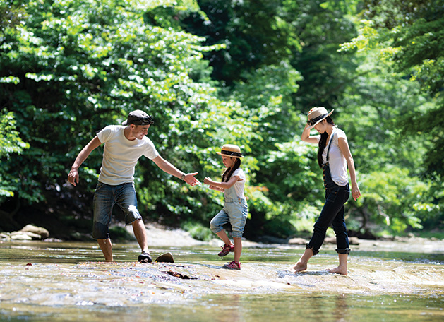 A couple on vacation with their child walks through a river.