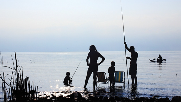 A family fishes on a lake while on vacation.