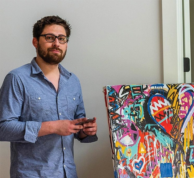 Painter Justin Hammer stands by one of his paintings.