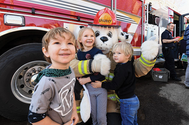 A firefighter dalmatian mascot poses with kids at the Our Savior Lutheran Church Easter Egg Hunt.