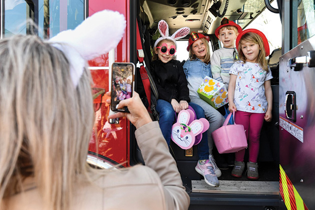 A woman takes a picture of kids in bunny ears holding Easter baskets.