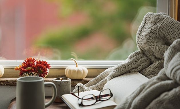 A cup of coffee sits near reading glasses and a book in a cozy nook.