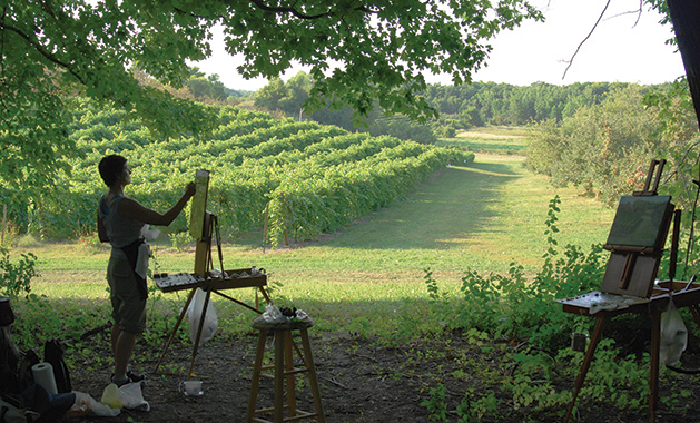A woman stands before a canvas, painting the grapevines at Parley Lake Winery.