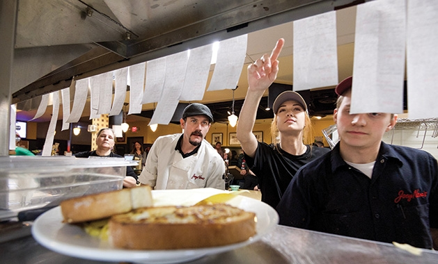 Joey Nova's Chef Gary Ezell and his employees review orders in the back kitchen.