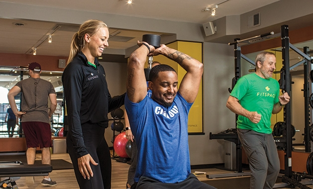 A personal trainer helps a man work out at Fitspace Wayzata, a no membership model fitness club.
