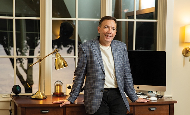 Paul Douglas leans on a desk in his Lake Minnetonka home.