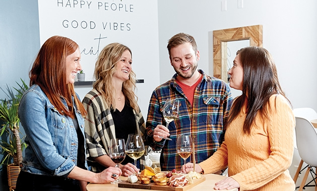 Friends gather around a table at The Vine Room in Hopkins