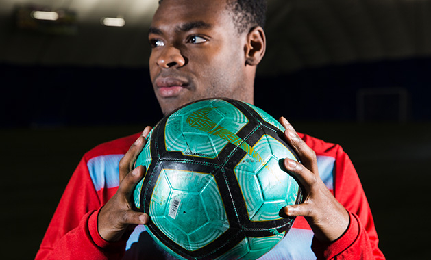 Orono grad Guy Mohs, originally from Haiti, holds a soccer ball.