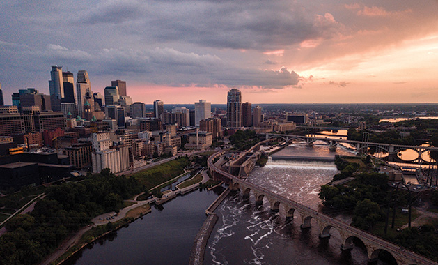 A shot of the Minneapolis skyline at sunset, with the Stone Arch Bridge in the foreground.