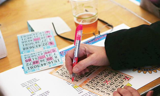 A person fills out their bingo card at the Bingo & Burgers by the Bay event.