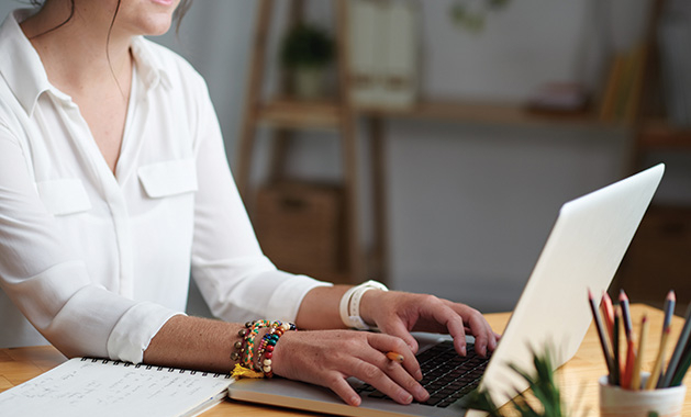 A woman sits working at a laptop with a pencil in hand and a notebook nearby.