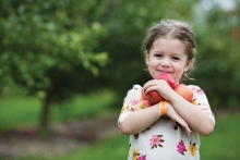 A girl holds apples at Apple Jack Orchards