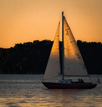 A sailboat sails at sunset on Lake Minnetonka.