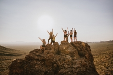 Group standing at the top of a rock.